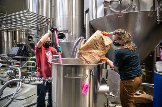 Odell Brewing employees stir up a batch of Allkind Hard Kombucha